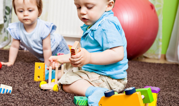 toddlers playing with wooden toys